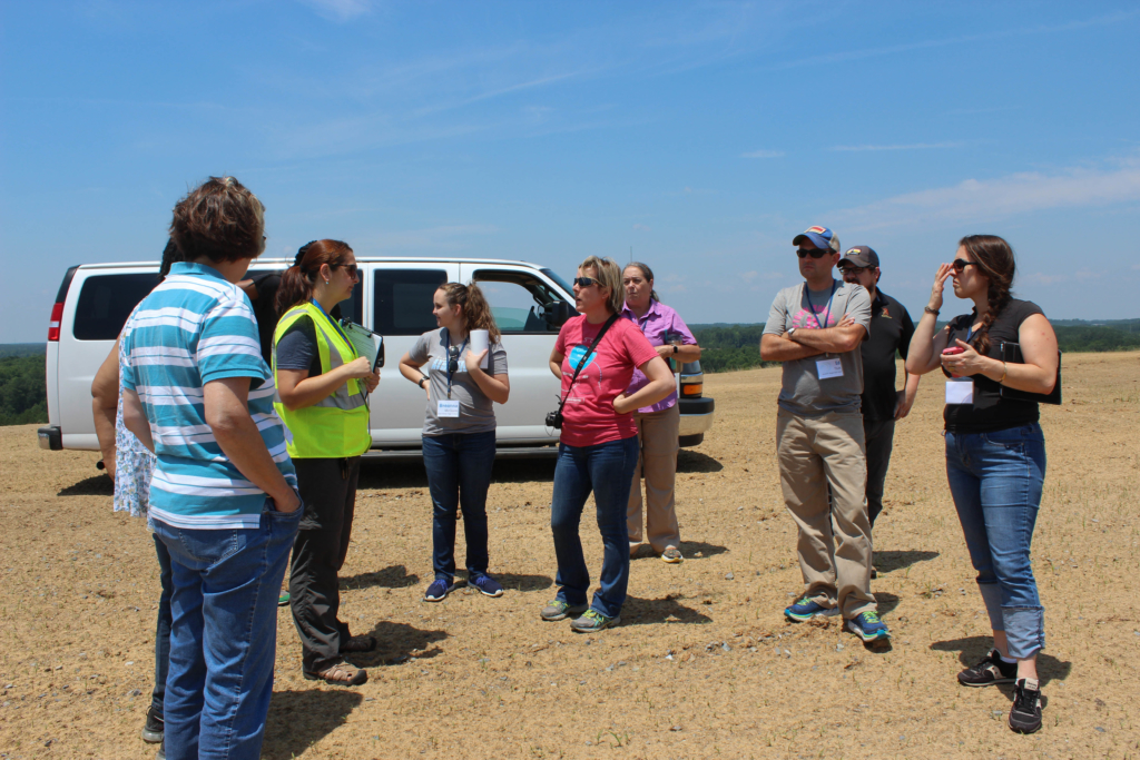 "Teachers stand on a completed landfill ""cell"" at South Wake Landfill. Yasmin Bendaas/EducationNC"