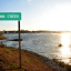 Town Creek sign in front of lake