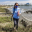 Postdoctoral researcher Stacy Zhang walks along the shoreline measuring oyster density to understand how the oyster reef that protects a blue carbon salt marsh habitat is growing.